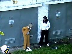 Two pretty office girls pee quietly in a yard