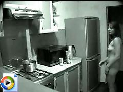 A nudist is taped by a secret camera in her kitchen here