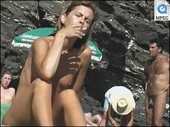 Nude girl caught smoking and sunbathing on a beach